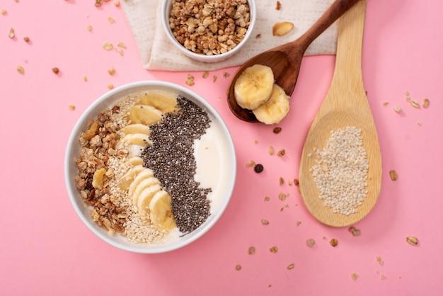 Gezonde ananas, mango smoothie bowl met kokos, bananen, bosbessen en granola. bovenaanzicht scène op een heldere