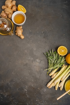 Gezonde antioxidant en ontstekingsremmende thee met verse ingrediënten gember, citroengras, salie, honing en citroen op donkere achtergrond met kopie ruimte. bovenaanzicht
