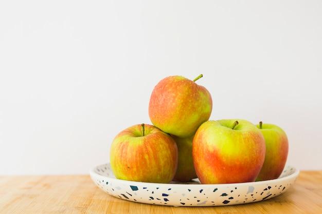 Gezonde appelen op plaat over het houten bureau tegen witte achtergrond