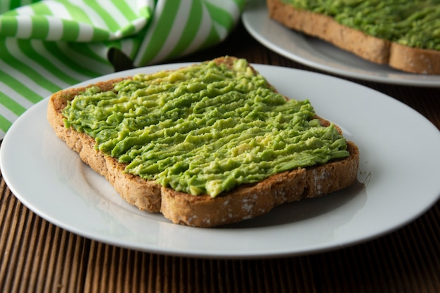 Gezonde avocado sandwich, toast brood. mushed avocadodeeg, op houten achtergrond. guacamole.