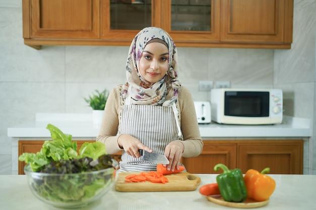 Gezonde aziatische moslimvrouw bereidt groenten voor om in de keuken te koken
