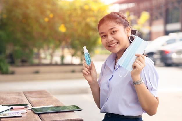Gezonde aziatische student blij met het gebruik van gezichtsmasker en alcoholspray op school voor bescherming tegen het coronavirus (covid-19).