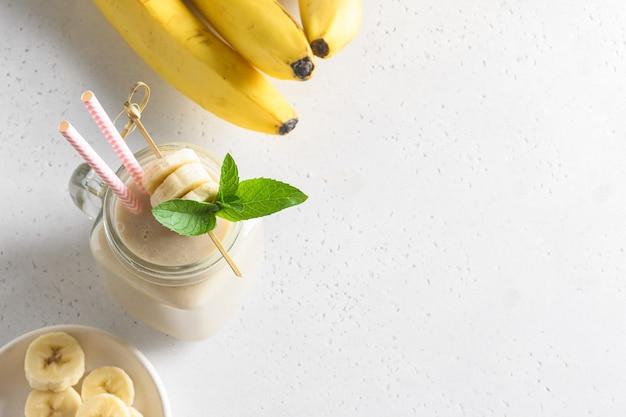 Gezonde banaanmilkshake in metselaarpot op witte achtergrond.