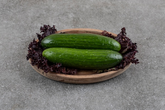 Gezonde biologische rijpe komkommers in houten plaat.