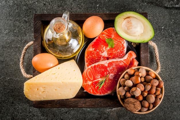 Gezonde biologische voeding. producten met gezonde vetten. omega 3, omega 6. ingrediënten en producten: forel (zalm), olijfolie, avocado, noten, kaas, eieren. op donkere stenen tafel. copyspace bovenaanzicht