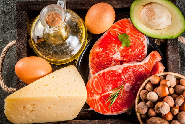 Gezonde biologische voeding producten met gezonde vetten omega 3 omega 6 ingrediënten en producten: forel (zalm) olijfolie avocado noten kaas eieren op donkere stenen tafel