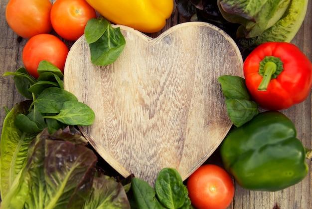 Gezonde biologische voeding, verse groenten in houten hart vorm vak op rustieke. bovenaanzicht met copyspace.