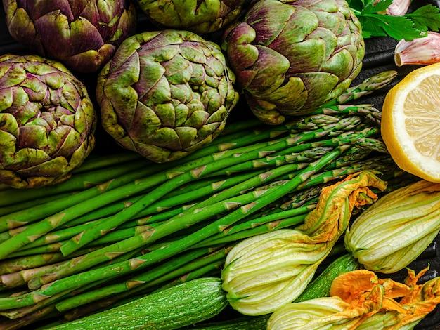 Gezonde biologische voedselruimte. artisjokken, asperges en zuccini met bloemen. bovenaanzicht