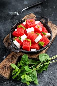 Gezonde biologische watermeloensalade met fetakaas. zwarte achtergrond. bovenaanzicht.