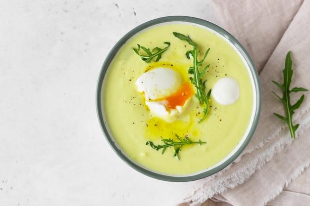 Gezonde bloemkoolsoep met gepocheerd ei, olijfolie en rucola in een keramische kom