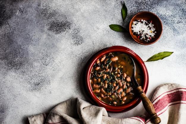 Gezonde bonensoep geserveerd in keramische kom op een tafel