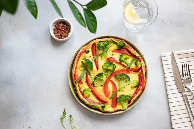 Gezonde broccoli en groene paprikaomelet op een grijs concreet vegetarisch ontbijt als achtergrond, horizontaal, exemplaarruimte