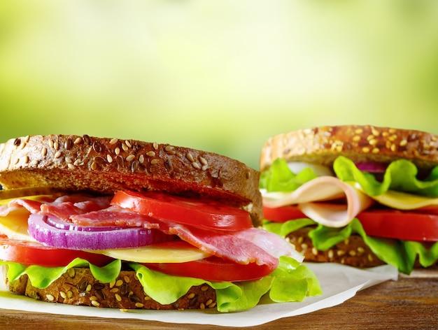 Gezonde broodjes vers bereid met spek, tomaat, ham, komkommer, kaas, ui op volkoren tarwe toast op houten tafel.