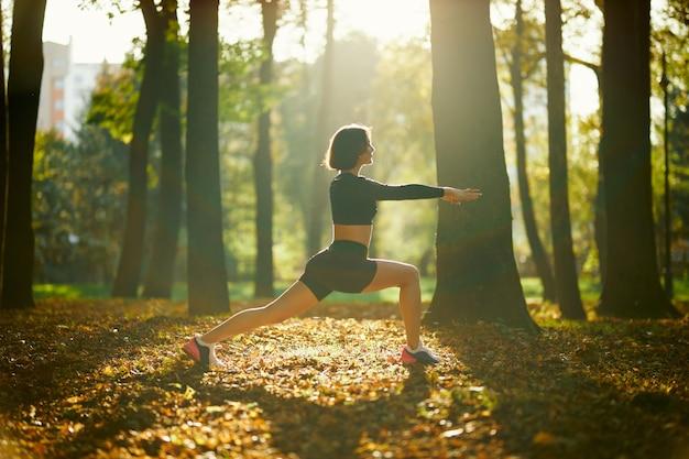Gezonde brunette die het lichaam uitrekt voor fitnessoefeningen