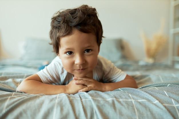 Gezonde charmante 3-jarige latijnse peuter liggend op verkreukelde lakens met de handen voor hem gevouwen, nieuwsgierig speelplezier met gezichtsuitdrukking