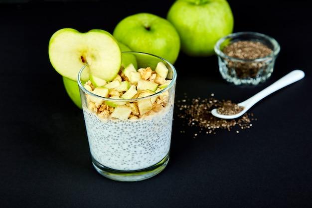 Gezonde chiapudding met appelen en granola in glas.