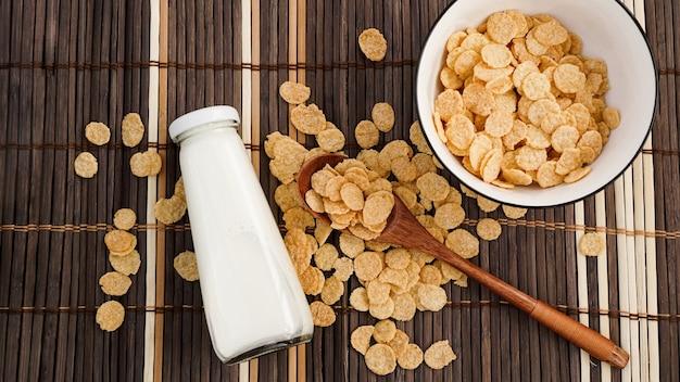 Gezonde cornflakes en melk en een houten lepel op een bamboeservet. glazen fles met melk voor een gezond ontbijt