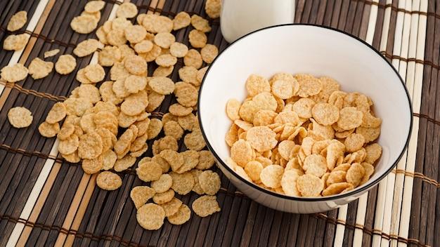 Gezonde cornflakes en melk op een bamboeservet. glazen fles met melk voor een gezond ontbijt