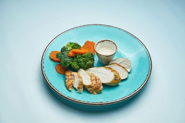 Gezonde, dieetvoeding - gebakken kipfilet met gekookte wortelen en broccoli in een blauwe keramische plaat geïsoleerd lichtgrijs oppervlak