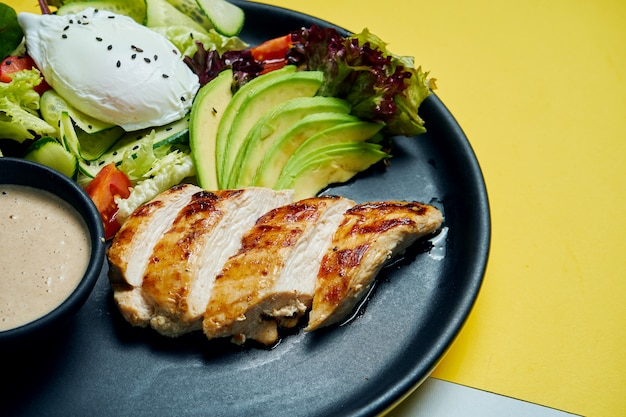 Gezonde, dieetvoeding - gebakken kipfilet met sla en gepocheerd ei in een zwarte keramische plaat op gekleurde oppervlak bovenaanzicht