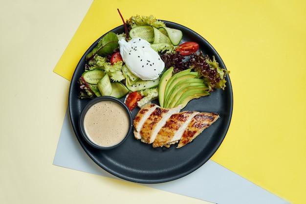 Gezonde, dieetvoeding - gebakken kipfilet met sla en gepocheerd ei in een zwarte keramische plaat op gekleurde oppervlak. bovenaanzicht