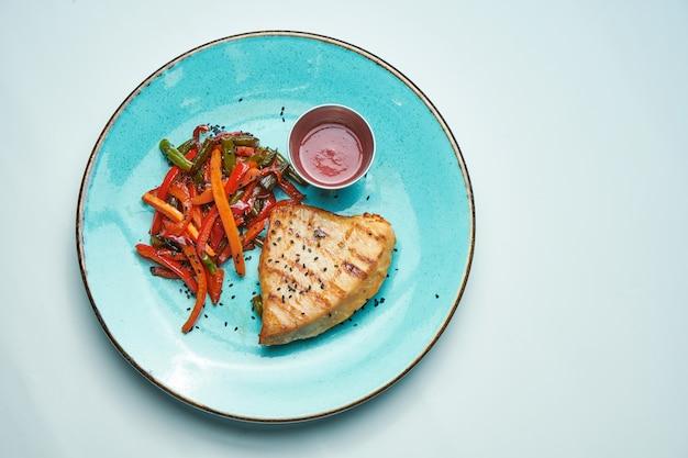 Gezonde, dieetvoeding - gegrilde kalkoenfilet met gekookte wortelen en broccoli in een blauwe keramische plaat geïsoleerd lichtgrijs oppervlak.