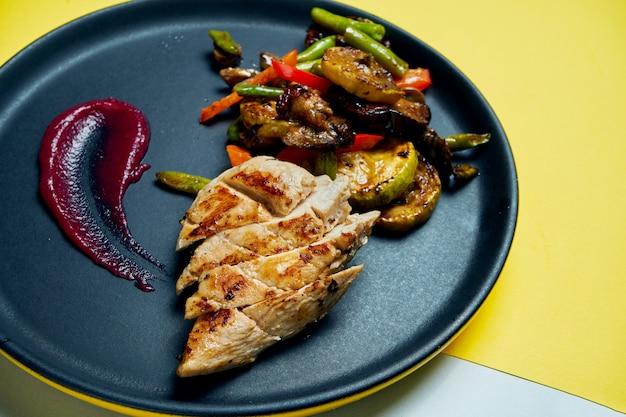 Gezonde, dieetvoeding - gegrilde kipfilet met gegrilde groenten in een zwarte keramische plaat op gekleurde ondergrond close up