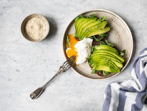 Gezonde eigengemaakte toosts met rucola en avocado op het brood van de roggekorrel en gepocheerd ei met het uitspreiden van dooier op plaat op grijze achtergrond. bovenaanzicht