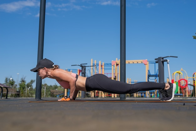 Gezonde en actieve levensstijl. sport en fitness. gelukkige vrouw in sportkleding die op zonnige zomerdag op het sportveld traint, haar buikspieren traint in plankpositie