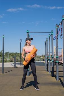 Gezonde en actieve levensstijl. sport en fitness. gelukkige vrouw in sportkleding die op zonnige zomerdag op het sportveld traint