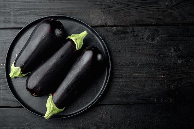 Gezonde en heerlijke paarse aubergines set, op zwarte houten tafel
