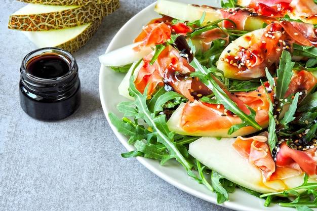 Gezonde en voedzame salade arugula melon prosciutto.