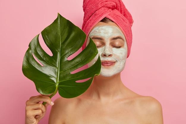Gezonde europese vrouw past gezichtsmasker toe voor verjonging en het verwijderen van poriën, houdt groen verlof vast, staat met gesloten ogen, naakt lichaam, gewikkelde handdoek op hoofd, modellen binnen. cosmetologie, schoonheid