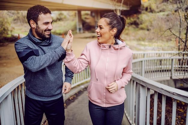 Gezonde fitte jonge vrienden lopen, de brug op en geven elkaar high five. het doel is bereikt. fitness buitenshuis concept.