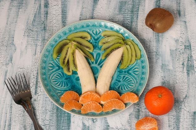 Gezonde fruitsalade voor kinderen van kiwi, bananen en mandarijnen in de vorm van een palmboom