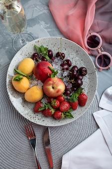 Gezonde fruitschotel, aardbeien, appels, perziken, abrikozen op een donkergrijze houten tafel, bovenaanzicht, close-up, selectieve aandacht.