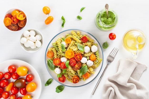 Gezonde fusilli pasta met pestosaus, geroosterde tomaten, mozzarella