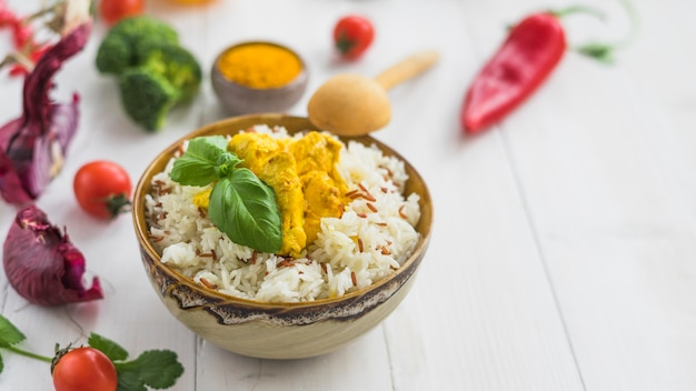 Gezonde gefrituurde rijst met kip; ui; kersentomaat en rode spaanse peperpeper over wit bureau