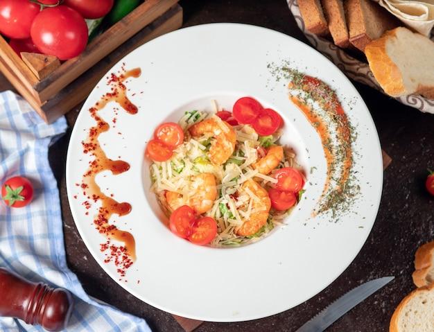 Gezonde gegrilde crevettes caesar salade met kaas, cherry tomaten en sla