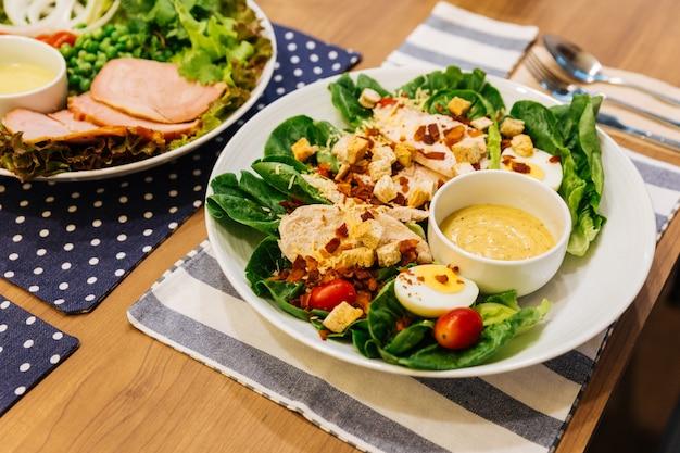 Gezonde gegrilde kip caesar salade met kaas, croutons, groene eik, gekookt ei en cris