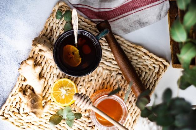 Gezonde gemberthee met citroen en honing op rustiek