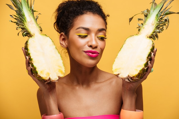 Gezonde gemengd rasvrouw met maniermake-up die detox hebben die verse rijpe ananas houden die in half geïsoleerd, over gele muur wordt verdeeld