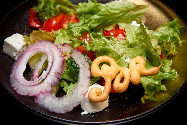 Gezonde gemengde salade met greens, komkommer, ui, tomaten en feta-kaas.