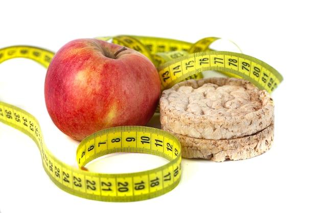 Gezonde gepofte maïs galettes en rode appel met meetlint op witte achtergrond.