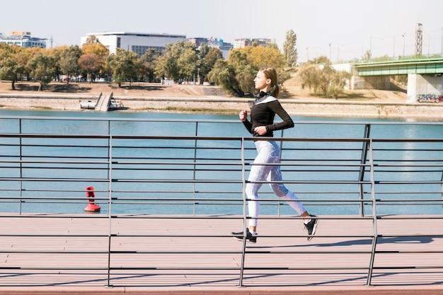 Gezonde geschiktheids sportieve vrouwelijke agent die dichtbij het meer loopt