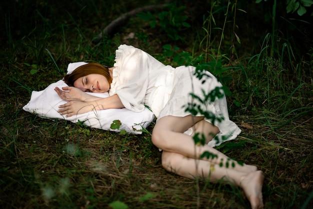 Gezonde gezonde slaap. rust, ontspanning in het bos. vrouw slaapt op een kussen op een groene open plek in het bos.