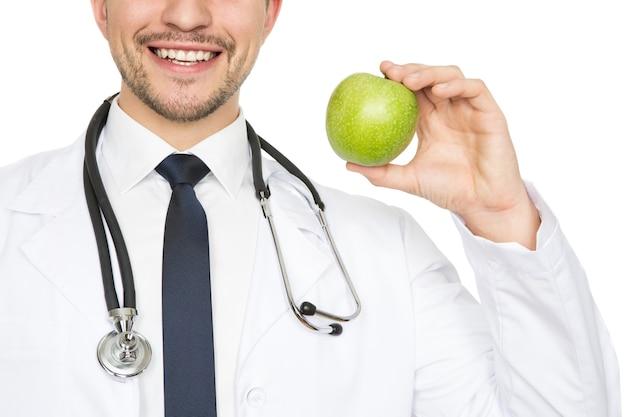 Gezonde glimlach. bijgesneden close-up shot van een mannelijke arts glimlachend gelukkig met een appel geïsoleerd op wit