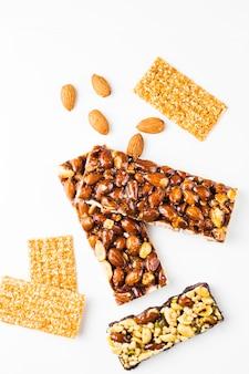 Gezonde granola; amandel- en sesamrepen tegen een witte achtergrond