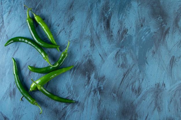 Gezonde groene chilipepers geplaatst op blauwe achtergrond.