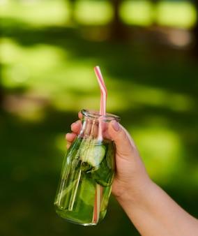 Gezonde groene detox-drank op zomergras in de hand. verse koude theepot buitenshuis.